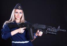 Mujer joven hermosa en un uniforme marino con un rifle de asalto Imagen de archivo