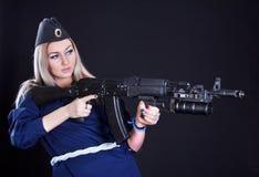 Mujer joven hermosa en un uniforme marino con un rifle de asalto Fotografía de archivo
