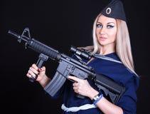 Mujer joven hermosa en un uniforme marino con un rifle de asalto Foto de archivo