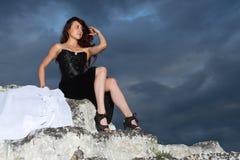 Mujer joven hermosa en un vestido negro imagenes de archivo