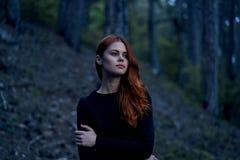 Mujer joven hermosa en un vestido negro en el bosque Fotos de archivo libres de regalías