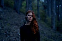 Mujer joven hermosa en un vestido negro en un bosque oscuro Imágenes de archivo libres de regalías