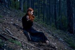 Mujer joven hermosa en un vestido negro largo en el bosque Imágenes de archivo libres de regalías