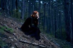 Mujer joven hermosa en un vestido negro largo en el bosque Imagenes de archivo