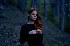 Mujer joven hermosa en un vestido negro largo en el bosque Fotos de archivo