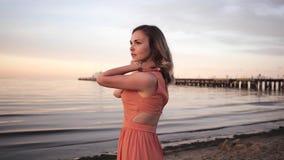 Mujer joven hermosa en un vestido que presenta a lo largo de la costa que sonríe en la puesta del sol cerca del mar almacen de video
