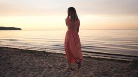 Mujer joven hermosa en un vestido que presenta a lo largo de la costa que sonríe en la puesta del sol cerca del mar almacen de metraje de vídeo