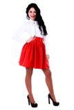 Mujer joven hermosa en una blusa blanca y una falda roja Fotos de archivo