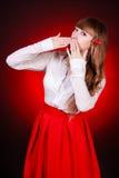 Mujer joven hermosa en una blusa camisera blanca y una falda roja Imágenes de archivo libres de regalías