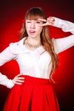 Mujer joven hermosa en una blusa camisera blanca y una falda roja Foto de archivo libre de regalías