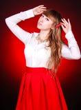 Mujer joven hermosa en una blusa camisera blanca y una falda roja Fotografía de archivo