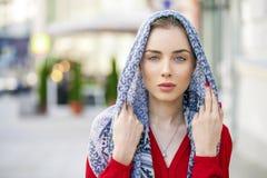 Mujer joven hermosa en una bufanda azul en ciudad de la calle del verano Foto de archivo libre de regalías