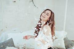Mujer joven hermosa en una cama que cae las plumas y la sonrisa Retrato horizontal del primer Fotografía de archivo libre de regalías