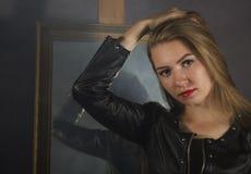 Mujer joven hermosa en una chaqueta de cuero que presenta en un fondo del espejo