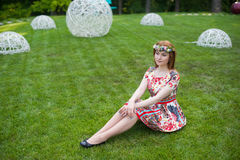 Mujer joven hermosa en una guirnalda de flores y un vestido brillante que se sienta en el retrato en naturaleza, la alegría de la Fotos de archivo