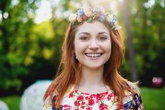 Mujer joven hermosa en una guirnalda de flores y un vestido brillante que se sienta en el retrato en naturaleza, la alegría de la Imagen de archivo