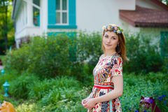 Mujer joven hermosa en una guirnalda de flores y un vestido brillante que se sienta en el retrato en naturaleza, la alegría de la Foto de archivo libre de regalías