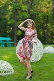 Mujer joven hermosa en una guirnalda de flores y un vestido brillante que se sienta en el retrato en naturaleza, la alegría de la Fotografía de archivo libre de regalías