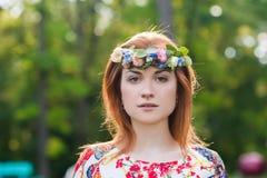 Mujer joven hermosa en una guirnalda de flores y un vestido brillante que se sienta en el retrato en naturaleza, la alegría de la Foto de archivo
