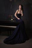 Mujer joven hermosa en vestido negro al lado de un piano con las velas y el vino, atmósfera dramática oscura de los candelabros d Imagen de archivo