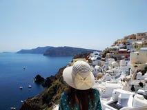Mujer joven hermosa en vestido punteado verde que camina en Oia, calles de Santorini Casas blancas, mar azul fotos de archivo libres de regalías