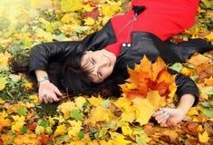 Mujer joven hermosa en vestido rojo en hojas de arce Fotos de archivo