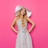 Mujer joven hermosa en vestido y el sombrero punteados de Sun del blanco Imagen de archivo libre de regalías