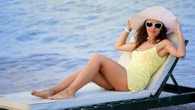 Mujer joven hermosa en vidrios que toma el sol en la playa contra el mar almacen de video
