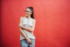 Mujer joven hermosa en vidrios En un fondo rojo hermoso Belleza, manera maquillaje Foto de archivo