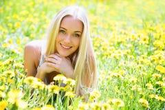 Mujer joven hermosa entre las flores imagen de archivo