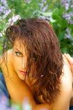 Mujer joven hermosa entre las flores Fotografía de archivo