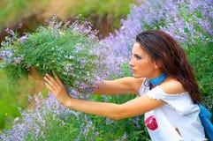 Mujer joven hermosa entre las flores Imágenes de archivo libres de regalías
