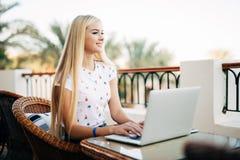 Mujer joven hermosa, estudiante que se sienta en terraza, en café, trabajando en el ordenador portátil, disfrutando del trabajo s imagen de archivo libre de regalías