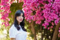 Mujer joven hermosa feliz cerca del árbol del flor en jardín fotografía de archivo libre de regalías