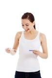 Mujer joven hermosa feliz con la prueba de embarazo. Foto de archivo libre de regalías