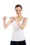 Mujer joven hermosa feliz con la prueba de embarazo. Fotografía de archivo