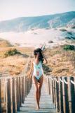 Mujer joven hermosa feliz con un traje de natación que corre en un wo fotografía de archivo libre de regalías