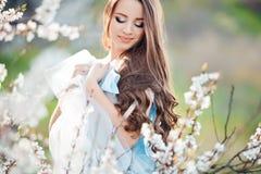 Mujer joven hermosa feliz en parque del flor de la primavera Fotos de archivo