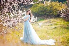 Mujer joven hermosa feliz en parque del flor de la primavera Imagen de archivo libre de regalías