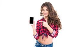 Mujer joven hermosa feliz que sostiene el teléfono móvil de la pantalla en blanco Fotografía de archivo