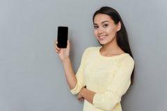 Mujer joven hermosa feliz que sostiene el teléfono móvil de la pantalla en blanco Fotografía de archivo libre de regalías