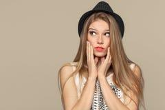 Mujer joven hermosa feliz sorprendida que mira para arriba en el entusiasmo Muchacha de la moda en sombrero Aislado en fondo beig Imágenes de archivo libres de regalías
