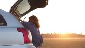 Mujer joven hermosa feliz y que baila en un tronco de coche durante un viaje por carretera en Europa en los minutos pasados de la almacen de video
