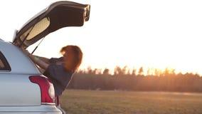 Mujer joven hermosa feliz y que baila en un tronco de coche durante un viaje por carretera en Europa en los minutos pasados de la almacen de metraje de vídeo