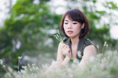 Mujer joven hermosa funning en hierba con las flores Fotos de archivo libres de regalías
