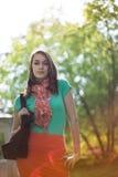 Mujer joven hermosa iluminada por el sol con el bolso de compras del paño fotos de archivo