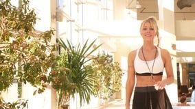 Mujer joven hermosa, instructor de una piscina de lujo del balneario pasos cerca y sonrisas en la c?mara 4K ?rboles tropicales en metrajes