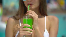 Mujer joven hermosa irreconocible en verano Muchacha del bikini que se relaja en piscina tropical mujer que bebe a almacen de metraje de vídeo