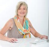 Mujer joven hermosa mayor que trabaja en la oficina con el ordenador Imagen de archivo libre de regalías