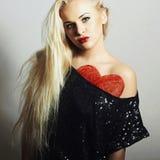Mujer joven hermosa Muchacha rubia Rose roja MUESTRA DEL CORAZÓN Fotos de archivo